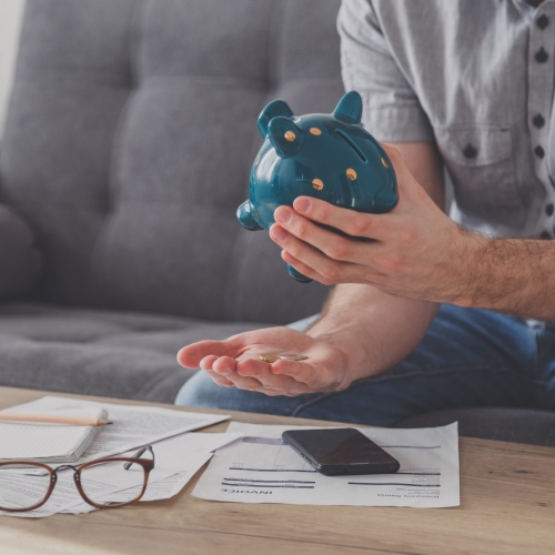 Man sitting at a table full of unpaid bills shakes out the last penny from the piggy bank. Spend your last savings. Unemployment, poverty, bankruptcy concept.